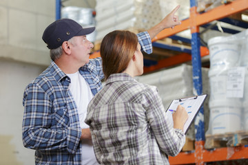 workers are looking a clipboard in a warehouse