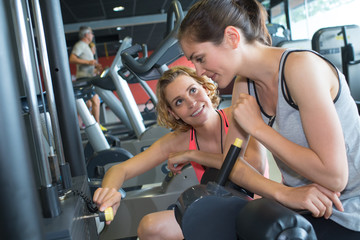 young woman with assistance of her female friend in gym