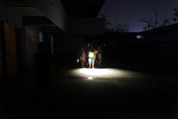 People who have lost their homes after Hurricane Maria hit the island in September, walk with the help of a flashlight at a school turned shelter, in Toa Baja