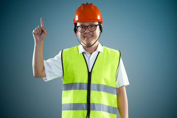 Young asian construction workers in safety helmet pointing up the finger ,isolated on blue background .