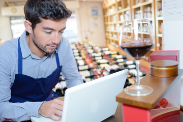 wine store seller using a laptop