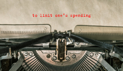 to limit one's expense is printed on an old vintage typewriter, in red letters. close-up