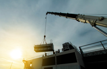 mobile crane lifting Cooling machine, silhouettes at sunset