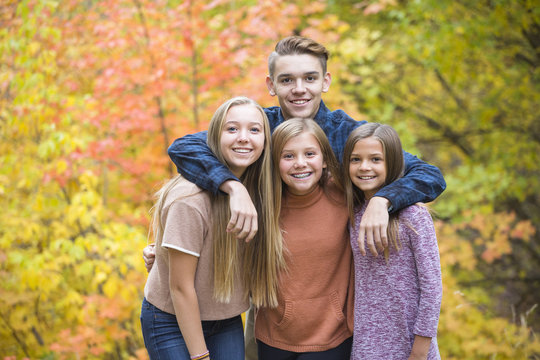 Beautiful Portrait of smiling happy teen kids outdoors. Four siblings standing together for a cute picture on a warm fall day