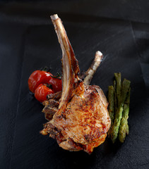 grilled lamb steak with asparagus and tomatoes on a black background