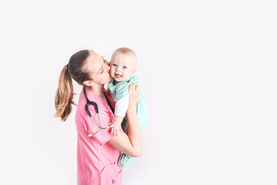 Nurse mother holding her baby dressed up in scrubs