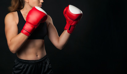 Female boxer with the red boxing gloves, black background with copy space