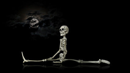 Halloween skeleton stretching at night in front of a nice cloud covered moon.