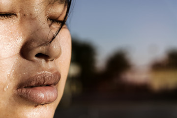 Closeup  sweating on face of Asian women .  Exercise for health In urban city Park.