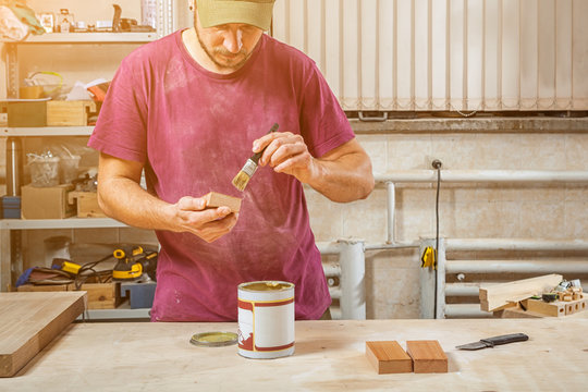 Close-up The man carpenter in working clothes paints a wooden block with a brown protective paint from Corrrosia on a wooden desktop, on which there is a paint, a spatula in the workshop
