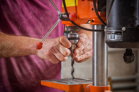 Close-up of a man carpenter in work clothes drilling  on an orange large measuring machine in a light workshop