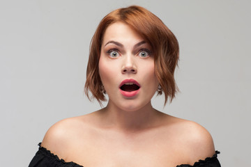 Shocking news. Surprise for birthday, good news, big size concept. Female emotion of astonishment, beautiful amazed woman on grey background
