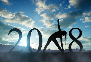 Silhouette of a girl practicing yoga in the New Year 2018.