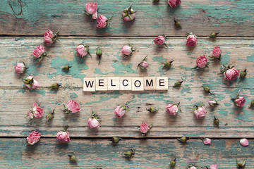 Welcome sign and pink roses on wooden background.