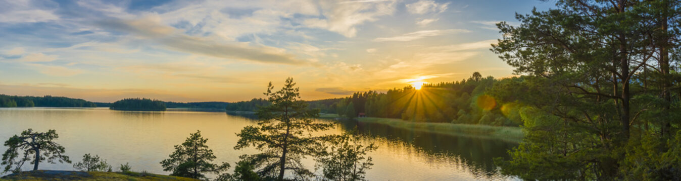 Panorama picture taken in Sweden with sunset over a lake and beautiful glow from the sun