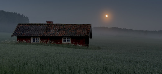 red house in the middle of a field in the middle of the night with fog and moon creating a mystical feel to the photo
