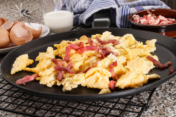 scrambled eggs with bacon in a pan