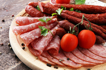 Food tray with delicious salami, pieces of sliced ham, sausage, tomatoes, salad and vegetable - Meat platter with selection - Cutting sausage and cured meat