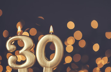Gold number 30 celebration candle against blurred light background