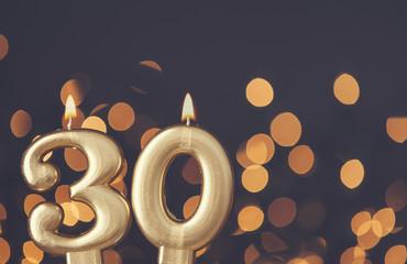 Gold number 30 celebration candle against blurred light background