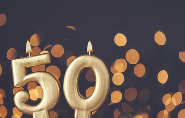 Gold number 50 celebration candle against blurred light background