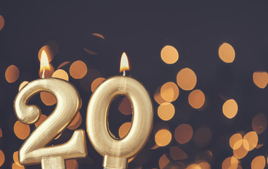 Gold number 20 celebration candle against blurred light background