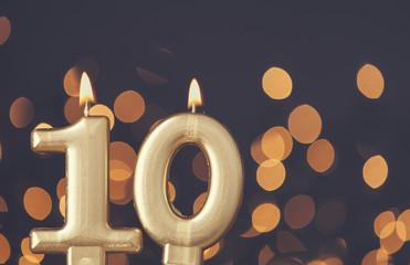 Gold number 10 celebration candle against blurred light background