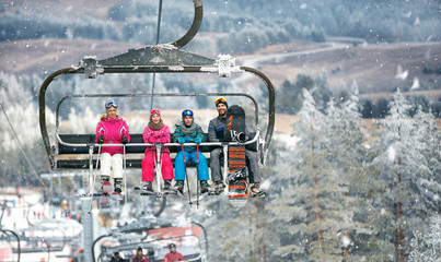 Parents with children in the ski lift  climbs on the ski terrain