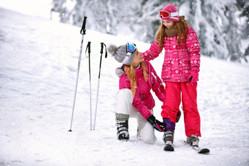 Mother fixing pants to daughter on ski terrain