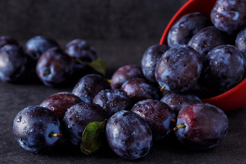 ripe plums over dark table background close up.