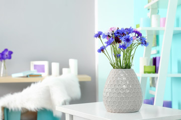 Lilac accent in modern interior. Vase with beautiful cornflowers on table in living room