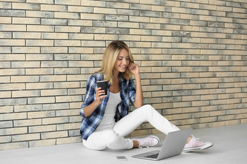 Pretty woman with modern laptop sitting near brick wall