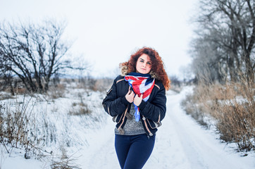 a young girl walks in the field. Dressed in winter clothes, she has blue eyes and thick red hair . Hair curls , the color of fire .