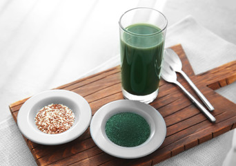 Spirulina drink, powder and seeds on wooden board