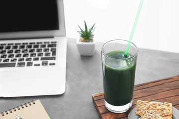 Glass with spirulina drink near laptop on table