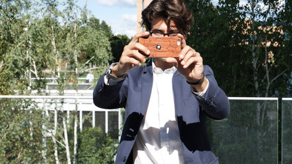 Handsome young man in city setting, taking photos with cell phone of the person behind the camera. POV of person being photographed