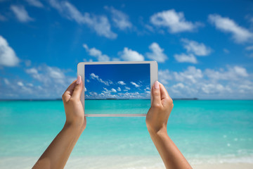Woman holding tablet computer with screen on the tropical sea. travel concept - tourist photograph tropical beach on tablet pc.