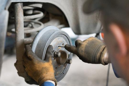 Close-up repair drum brake of car wheel in garage.