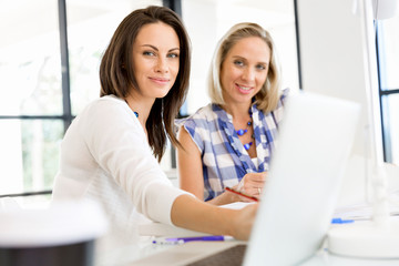 Image of two young business women in office