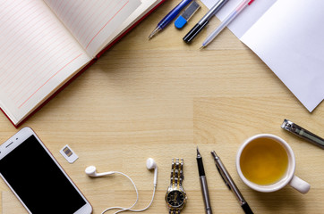 blank notebook with pen on wood table And a wrist watch headset Modern phone Tea