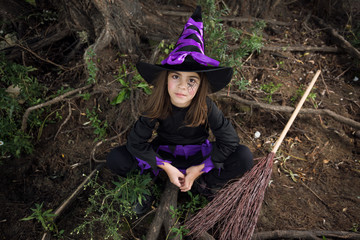 little witch outdoors in halloween