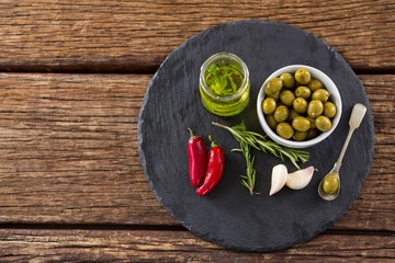 Green olives, fresh herbs with olive oil and red chilies on