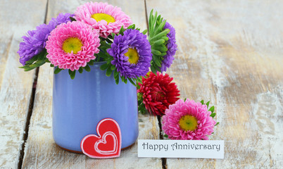 Happy birthday card with colorful pink daisies in blue vase on rustic wooden surface