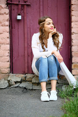 Lifestyle moment,hippie woman sitting looking away in beautiful street place, puffy background , pink, wooden door burgundy