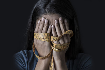 hands wrapped in tailor measure tape covering face of young depressed and worried girl suffering anorexia or bulimia nutrition disorder