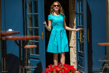 Feminine young woman in sunglasses, smiling looking camera, in blue dress, blue door, red flowers, outdoor, street style