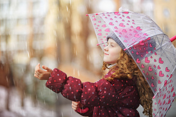 Little girl catches raindrops in autumn park.
