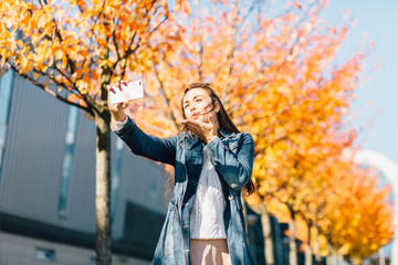 Pretty hipster girl in jeans coat trench taking selfie, smiling and sending air kiss in sunny autumn day. Education, lifestyle and travel concept.