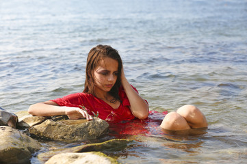 Fashion girl in the water. Sad girl on the sea. Beautiful girl in a wet red dress.