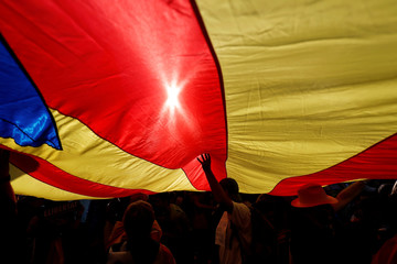 People stand under a giant separatist Catalonian flag during a demonstration organised by Catalan pro-independence movements ANC (Catalan National Assembly) and Omnium Cutural, following the imprisonment of their two leaders, in Barcelona